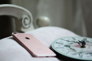 iPhone and clock in bed_1500